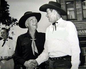 Fuera de escena, el villano Glenn Strange estrecha la mano de su rival, William Boyd (Hopalong Cassidy)